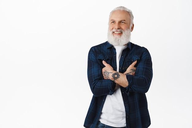Homem bonito e hippie sênior parecendo satisfeito com o logotipo da promoção, um cara velho e elegante com tatuagens cruzadas de braços no peito, olhando para o lado com um rosto sorridente satisfeito, em pé sobre uma parede branca