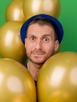 Homem bonito e impressionado com um chapéu de festa azul segurando balões de hélio olhando para a frente, isolados na parede verde
