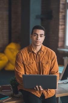 Homem bonito e inteligente em pé com seu laptop enquanto pensa em seu trabalho