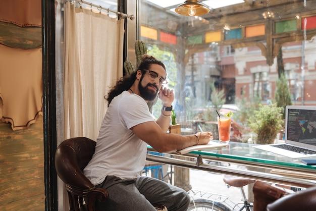 Homem bonito e inteligente escrevendo um plano enquanto está sentado no café
