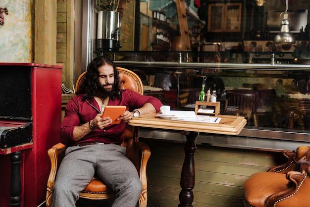 Homem bonito e inteligente usando tecnologia moderna enquanto está no café