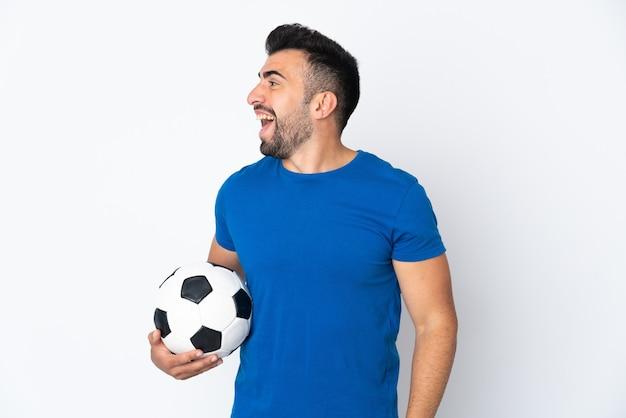 Homem bonito e jovem jogador de futebol sobre uma parede isolada rindo em posição lateral