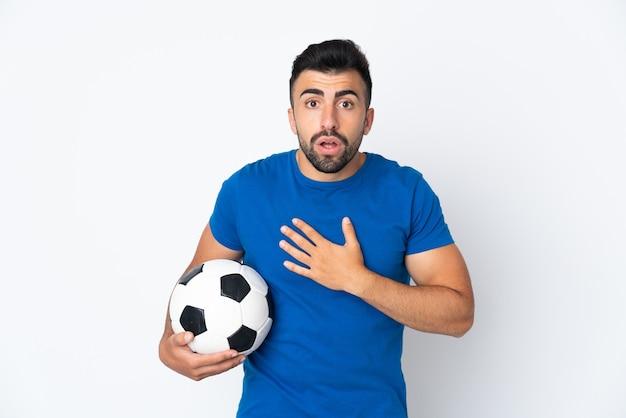 Homem bonito e jovem jogador de futebol sobre uma parede isolada surpreso e chocado ao olhar para a direita