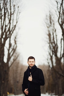 Homem bonito e jovem passeando sozinho no parque