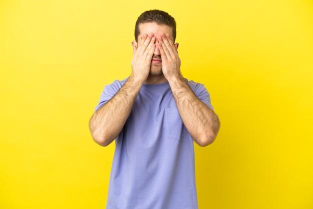 Homem bonito e loiro sobre fundo amarelo isolado, cobrindo os olhos com as mãos