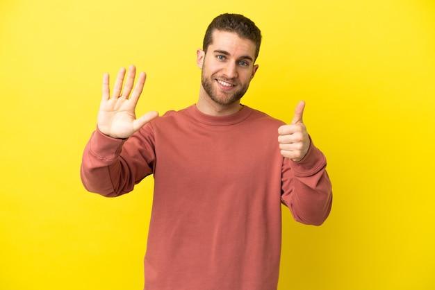 Homem bonito e loiro sobre fundo amarelo isolado, contando seis com os dedos