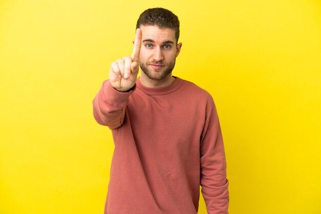 Homem bonito e loiro sobre fundo amarelo isolado contando um com expressão séria