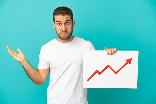 Homem bonito e loiro sobre fundo azul isolado segurando uma placa com um símbolo de seta de estatísticas crescentes, tendo dúvidas