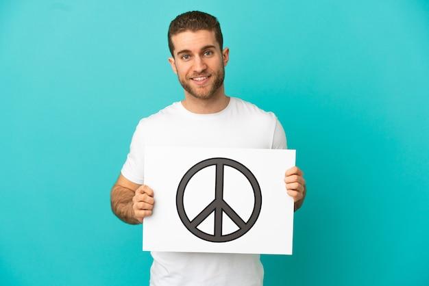 Homem bonito e loiro sobre um fundo azul isolado, segurando um cartaz com o símbolo da paz e com uma expressão feliz