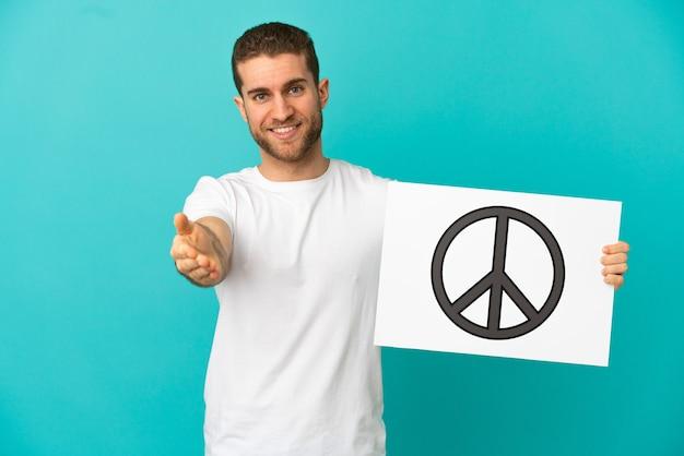 Homem bonito e loiro sobre um fundo azul isolado segurando um cartaz com o símbolo da paz fazendo um acordo