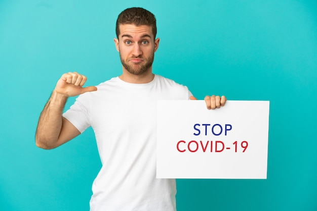 Homem bonito e loiro sobre um fundo azul isolado segurando um cartaz com o texto pare covid 19 com um gesto orgulhoso
