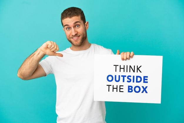 Homem bonito e loiro sobre um fundo azul isolado segurando um cartaz com o texto pense fora da caixa com um gesto orgulhoso