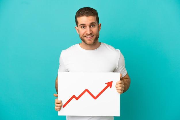 Homem bonito e loiro sobre um fundo azul isolado, segurando uma placa com um símbolo de seta de estatísticas crescentes com uma expressão feliz