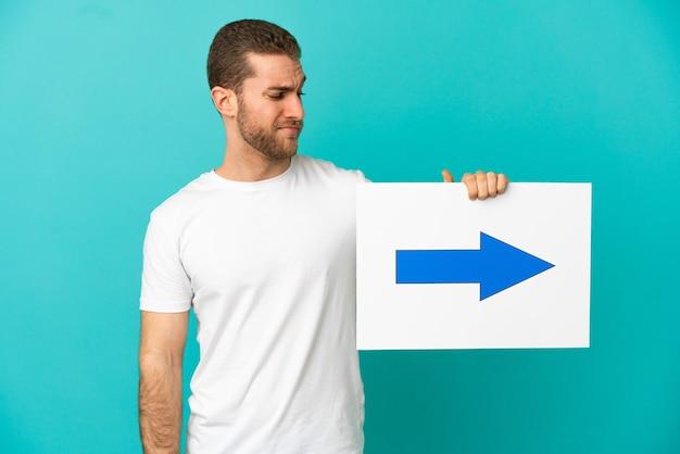 Homem bonito e loiro sobre uma parede azul isolada segurando um cartaz com o símbolo da seta