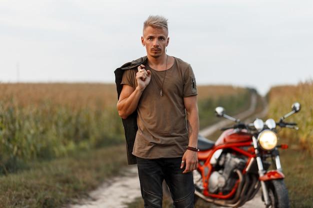 Homem bonito e moderno com uma jaqueta cáqui e uma camiseta verde e calça preta perto de uma motocicleta na natureza em um campo de milho