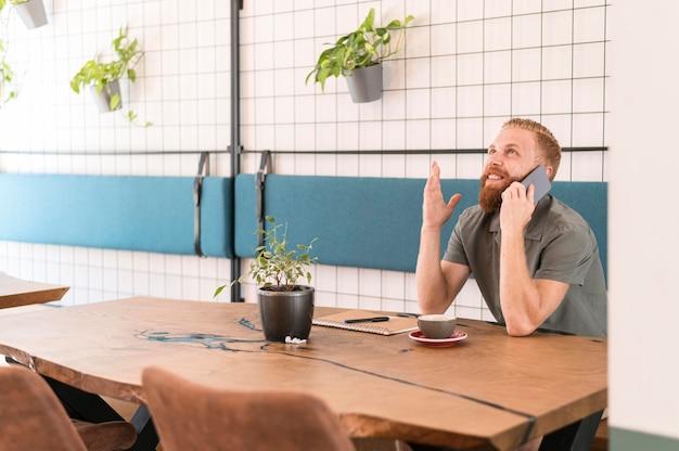 Homem bonito e moderno falando ao telefone com espaço de cópia