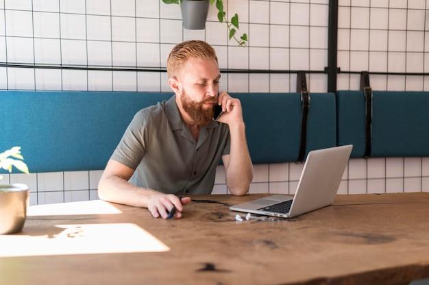 Homem bonito e moderno falando ao telefone enquanto trabalha