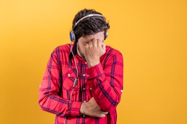 Homem bonito e moderno ouvindo música em fones de ouvido em amarelo
