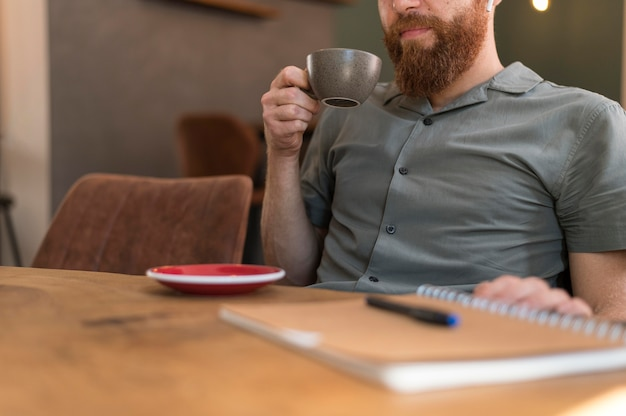 Homem bonito e moderno segurando uma xícara de café com espaço de cópia