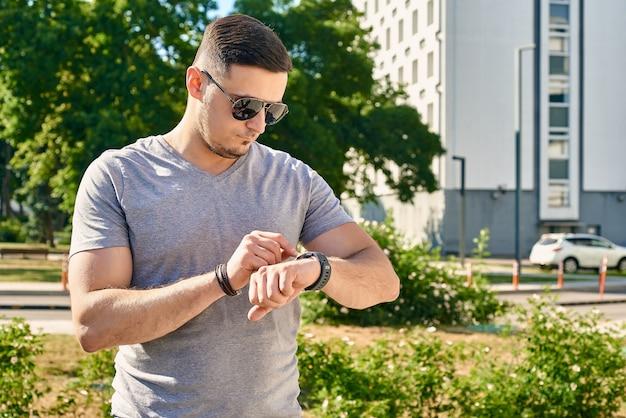 Homem bonito e musculoso de cabelo escuro usando óculos escuros ao ar livre olhando para um relógio inteligente