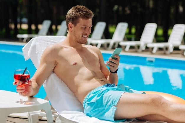 Homem bonito e musculoso lendo mensagem em seu smartphone azul enquanto se bronzea