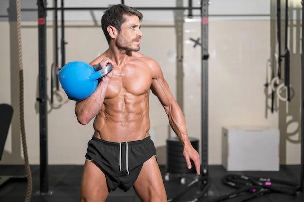 Homem bonito e musculoso levantando um kettlebell pesado