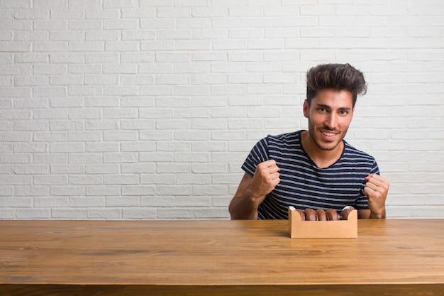 Homem bonito e natural jovem sentado em uma mesa muito feliz e animado, levantando os braços