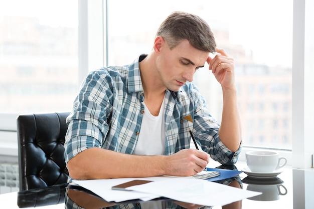 Homem bonito e pensativo com camisa quadriculada sentado à mesa com notas