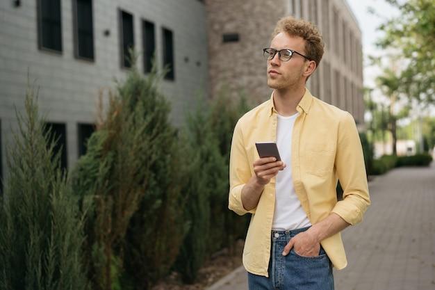 Homem bonito e pensativo, vestindo camisa amarela casual e óculos elegantes usando telefone celular