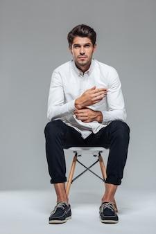 Homem bonito e relaxado desabotoando a manga da camisa e sentado na cadeira sobre a parede cinza