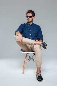 Homem bonito e relaxado em óculos de sol, sentado na cadeira sobre uma parede cinza