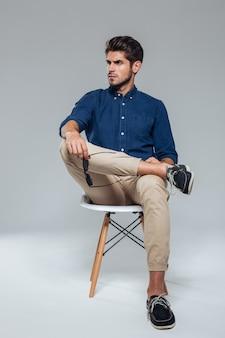 Homem bonito e relaxado segurando óculos escuros e sentado na cadeira sobre uma parede cinza