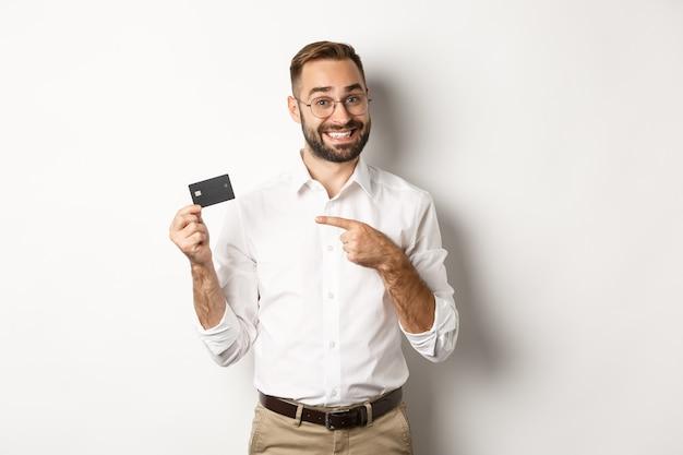 Homem bonito e satisfeito em copos, apontando para o cartão de crédito, satisfeito com os serviços bancários, sobre um fundo branco.