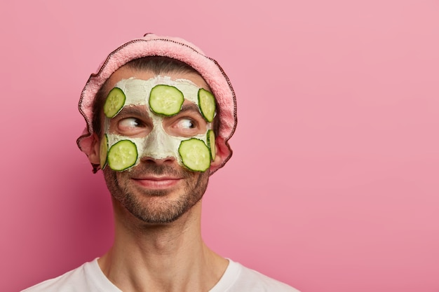 Homem bonito e satisfeito recebe tratamento facial, aplica máscara de argila com rodelas de pepino, gosta de procedimentos de beleza, tem cerdas