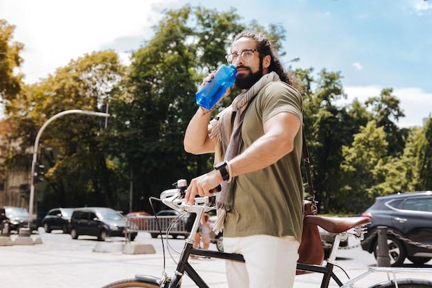 Homem bonito e sedento bebendo água em pé no meio da rua com sua bicicleta