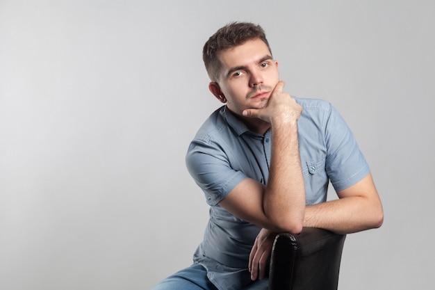 Homem bonito e sério sentado e pensando