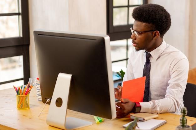 Homem bonito e sério verificando sua documentação enquanto pensa em sua nova estratégia de negócios
