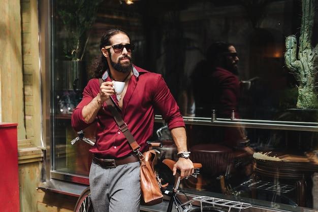 Homem bonito e simpático apreciando seu café em frente ao refeitório