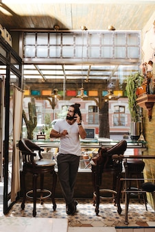 Homem bonito e simpático em pé no bar enquanto fala ao telefone