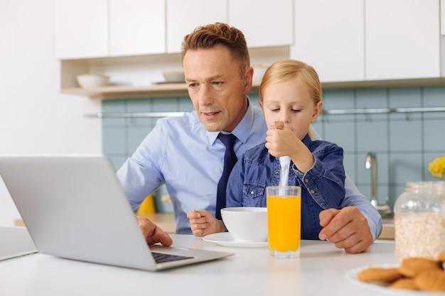 Homem bonito e simpático sentado à mesa da cozinha e usando um laptop enquanto sua filha está sentada no colo
