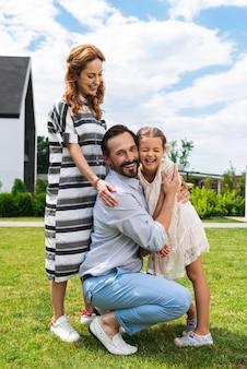 Homem bonito e simpático sorrindo enquanto abraça sua filha