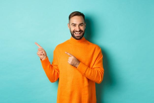 Homem bonito e sorridente apontando os dedos para a esquerda, mostrando seu logotipo, de pé no suéter laranja de inverno, parede turquesa.
