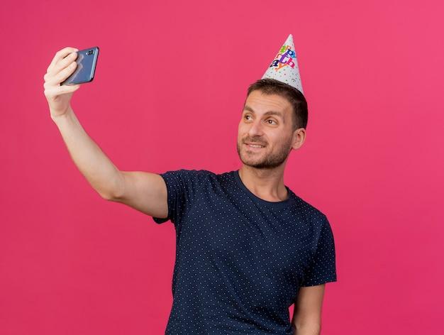 Homem bonito e sorridente caucasiano com boné de aniversário segura e olha para o telefone tirando uma selfie isolada no fundo rosa com espaço de cópia