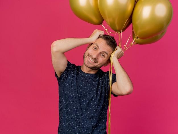 Homem bonito e sorridente caucasiano com chapéu de festa azul coloca as mãos na cabeça e segura balões de hélio isolados em um fundo rosa com espaço de cópia