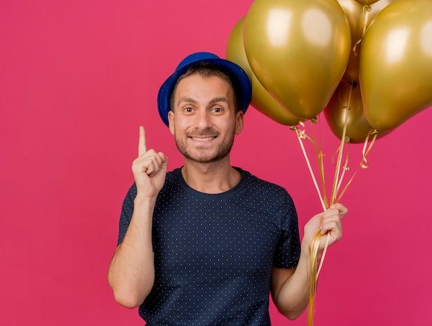 Homem bonito e sorridente caucasiano com chapéu de festa azul segurando balões de hélio apontando para cima isolados no fundo rosa com espaço de cópia