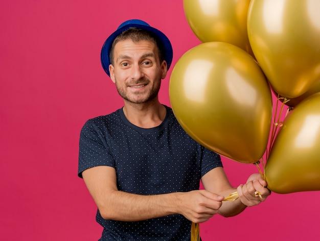 Homem bonito e sorridente caucasiano com chapéu de festa azul segurando balões de hélio isolados em um fundo rosa com espaço de cópia