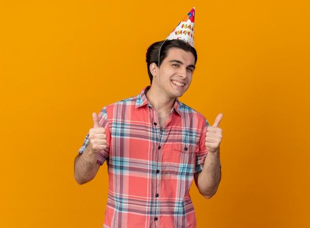 Homem bonito e sorridente caucasiano usando boné de aniversário com os polegares para cima com as duas mãos