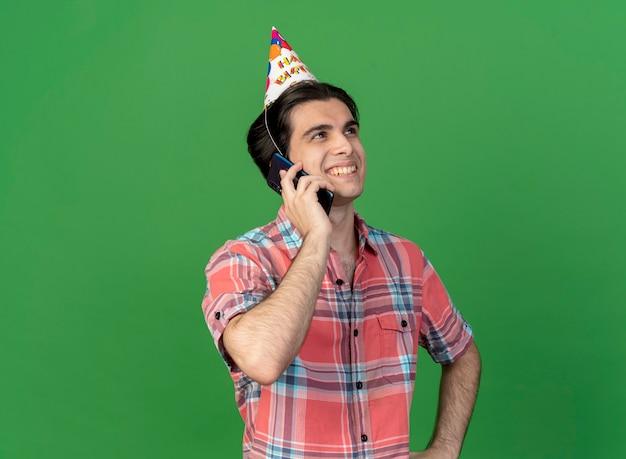 Homem bonito e sorridente caucasiano usando boné de aniversário fala ao telefone