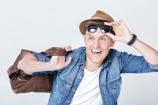 Homem bonito e sorridente com chapéu e óculos escuros carregando bolsa de couro no ombro