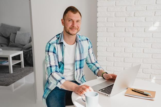 Homem bonito e sorridente com uma camisa, sentado na cozinha em casa, à mesa, trabalhando online no laptop de casa